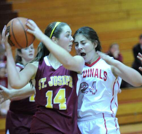 Erin Johnson #14 of St. Joseph looks to pass while being defended by Rebecca Kural # 24 of Greenwich during girls high school basketball game between Greenwich and St. Joseph at Greenwich High School, Tuesday night, Jan. 8, 2013. Photo: Bob Luckey / Greenwich Time