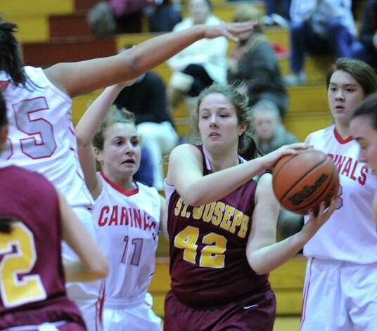 At center, Bridget Sharnick #42 of St. Joseph attempts to keep the ball away fro Alexa Moses # 11 of Greenwich during girls high school basketball game between Greenwich and St. Joseph at Greenwich High School, Tuesday night, Jan. 8, 2013. Photo: Bob Luckey / Greenwich Time