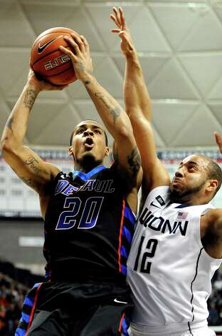 DePaul's Brandon Young, left, goes up for a basket while guarded by Connecticut's R.J. Evans during the first half of an NCAA college basketball game in Storrs, Conn., Tuesday, Jan. 8, 2013. Young had 35 points for DePaul. (AP Photo/Jessica Hill) Photo: Jessica Hill, Associated Press / FR125654 AP