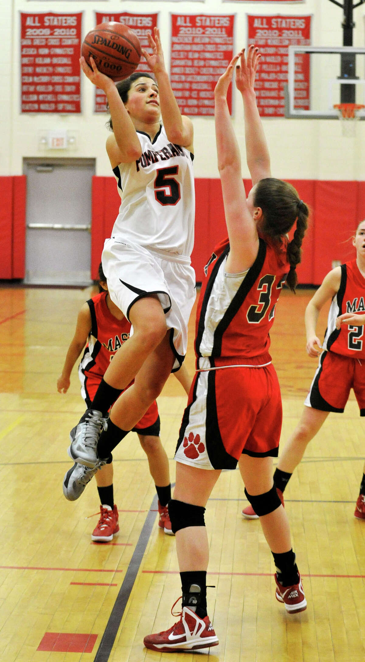 Pomperaug's Morgan Metcalf shoots over Masuk's Danielle Adams during their game at Pomperaug High School in Southbury on Tuesday, Jan. 8, 2013. Pomperaug won, 60-38.