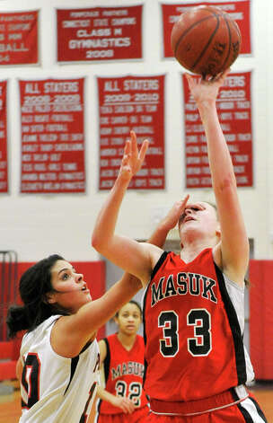 Pomperaug's Hannah Metcalf fouls Masuk's Danielle Adams during their game at Pomperaug High School in Southbury on Tuesday, Jan. 8, 2013. Pomperaug won, 60-38. Photo: Jason Rearick / The News-Times