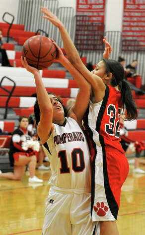 Pomperaug's Hannah Metcalf is fouled by Masuk's Thomese Holman during their game at Pomperaug High School in Southbury on Tuesday, Jan. 8, 2013. Pomperaug won, 60-38. Photo: Jason Rearick / The News-Times