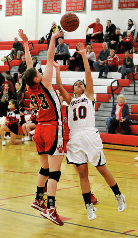 Pomperaug's Hannah Metcalf puts up a shot over Masuk's Danielle Adams during their game at Pomperaug High School in Southbury on Tuesday, Jan. 8, 2013. Pomperaug won, 60-38. Photo: Jason Rearick / The News-Times