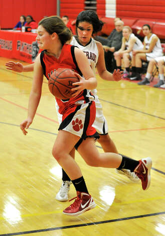 Masuk's Tori Schiebe drives along the baseline around Pomperaug's Hannah Metcalf during their game at Pomperaug High School in Southbury on Tuesday, Jan. 8, 2013. Pomperaug won, 60-38. Photo: Jason Rearick / The News-Times