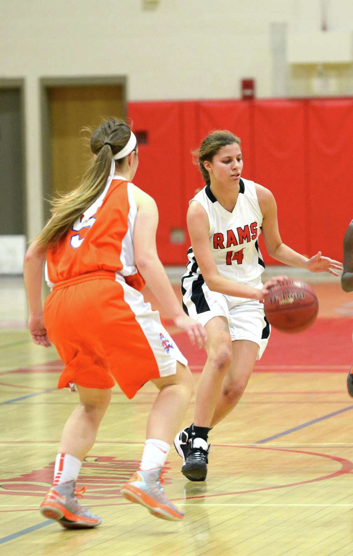 New Canaan's Colette Pellegrini (14) controls the ball as Danbury's Rachel Gartner (5) defends during the girls basketball game at New Canaan High School on Tuesday, Jan. 8, 2013.