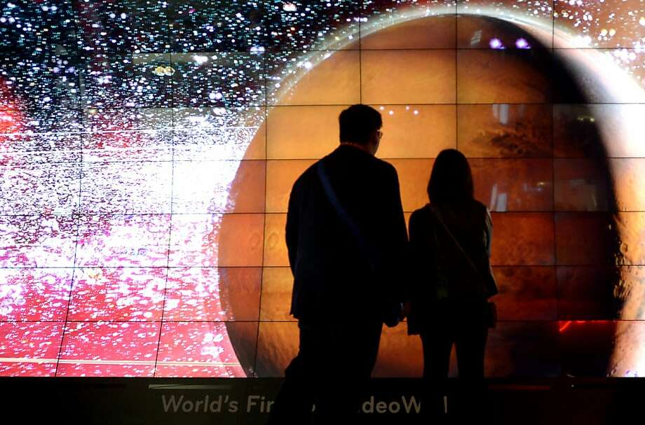 Attendees wearing 3-D glasses watch the world's first '3-D video wall' during a presentation at the LG booth during the 2013 International CES at the Las Vegas Convention Center on January 8, 2013 in Las Vegas, Nevada. CES, the world's largest annual consumer technology trade show, runs from January 8-11 and is expected to feature 3,100 exhibitors showing off their latest products and services to about 150,000 attendees. Photo: Joe Klamar, AFP/Getty Images