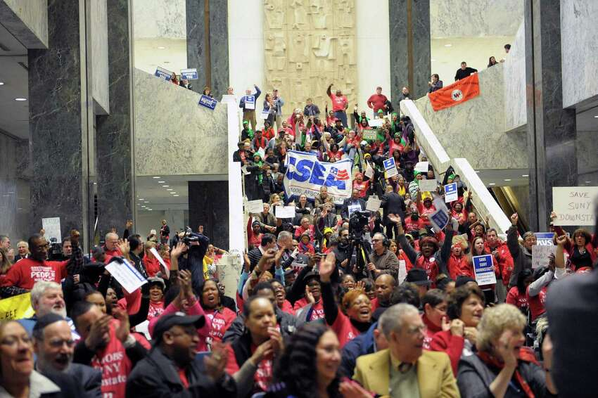 People cheer on a speaker during a rally at the Legislative Office Building on Tuesday, Jan. 8, 2013 in Albany, NY. Members of various unions along with leaders and members of community faith organizations and churches held the rally to show support for workers at SUNY's three public hospitals. Organizers of the rally say that thousands of jobs at the SUNY Downstate Medical Center's University Hospital of Brooklyn are to be eliminated as part of a financial restructuring. Organizers also say that their is talk of reducing services at the other SUNY hospitals as well. (Paul Buckowski / Times Union)