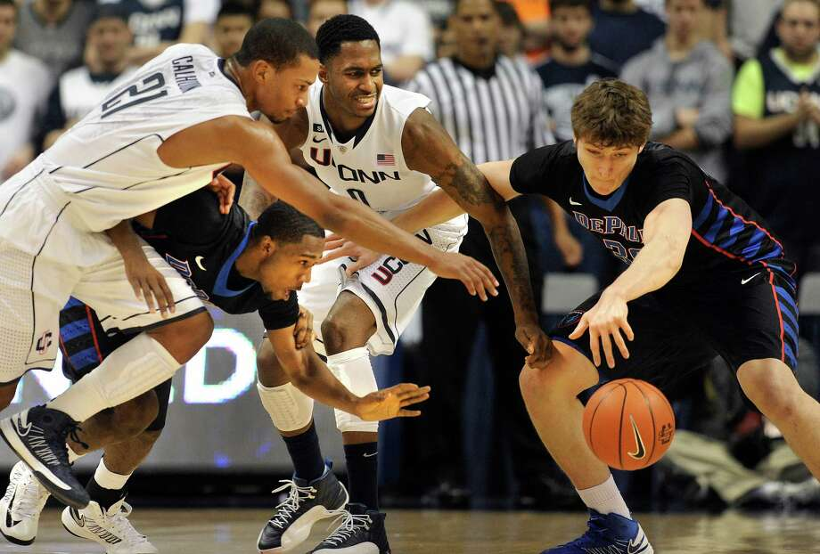 Connecticut's Omar Calhoun, left, and Phillip Nolan, center scramble for control of the ball against DePaul's Durrell McDonald, second from right, and Peter Ryckbosch, right, during the first half of an NCAA college basketball game in Storrs, Conn., Tuesday, Jan. 8, 2013. Photo: Jessica Hill