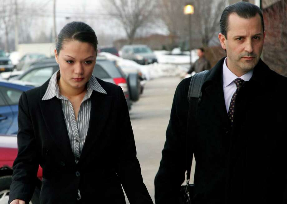 Dawn Nguyen, left, arrives with one of her lawyers at Henrietta Town Court Tuesday, Jan 8,  2013, in Rochester, N.Y. Nugyen is accused of lying on a form when she bought guns later used by ex-convict William Spengler Jr. to kill two firefighters and wound three others in Webster, N.Y.  (AP Photo/ Guy Solimano) Photo: Guy Solimano