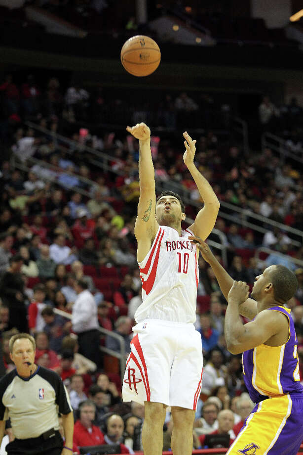 Rockets small forward Carlos Delfino puts up a shot over Lakers point guard Chris Duhon. Photo: Johnny Hanson / © 2012  Houston Chronicle