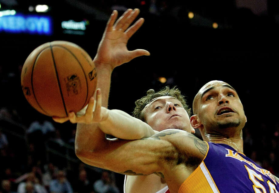 Rockets center Omer Asik battles for possession against Robert Sacre of the Lakers. Photo: Johnny Hanson / © 2012  Houston Chronicle