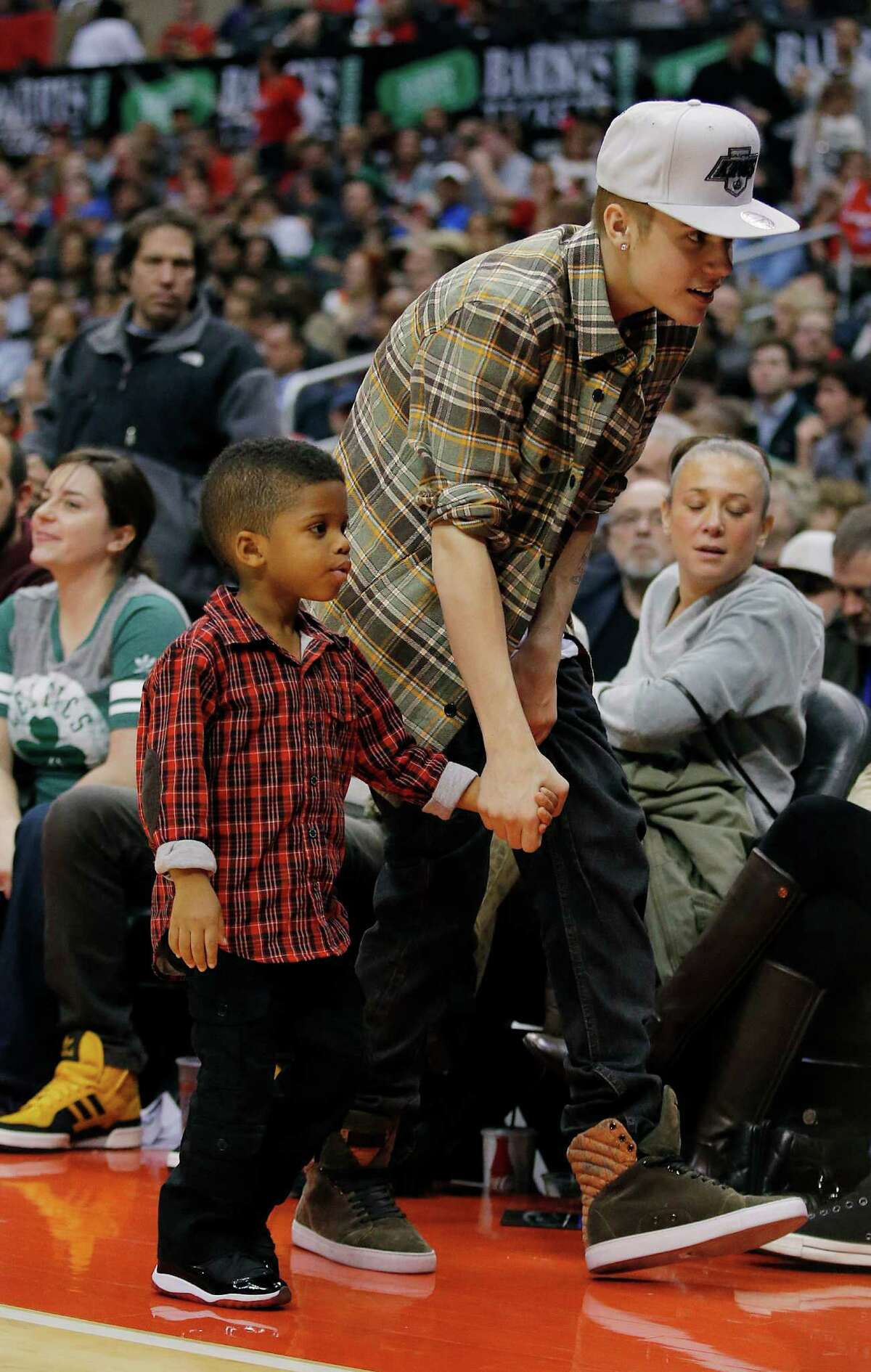 Singer Justin Bieber accompanies Los Angeles Clippers guard Chris Paul's son, Chris, during an NBA basketball game between the Los Angeles Clippers and the Boston Celtics in Los Angeles on Dec. 27, 2012.