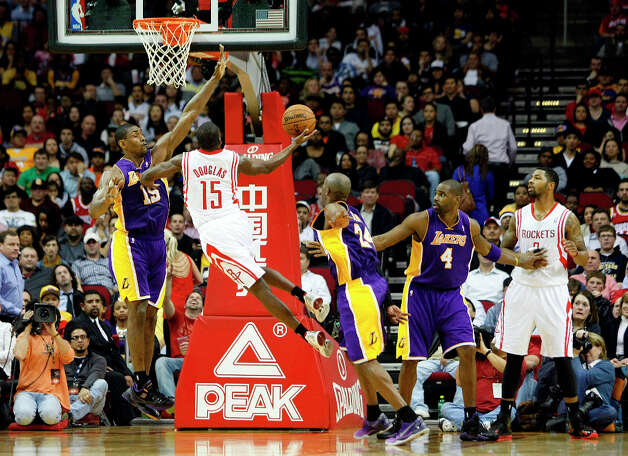 Houston Rockets point guard Toney Douglas (15) drives to the basket past Los Angeles Lakers small forward Metta World Peace (15) as the Houston Rockets defeated the Los Angeles Lakers 112 to 125 at Toyota Center Tuesday, Jan. 8, 2013, in Houston. Photo: Johnny Hanson / © 2012  Houston Chronicle