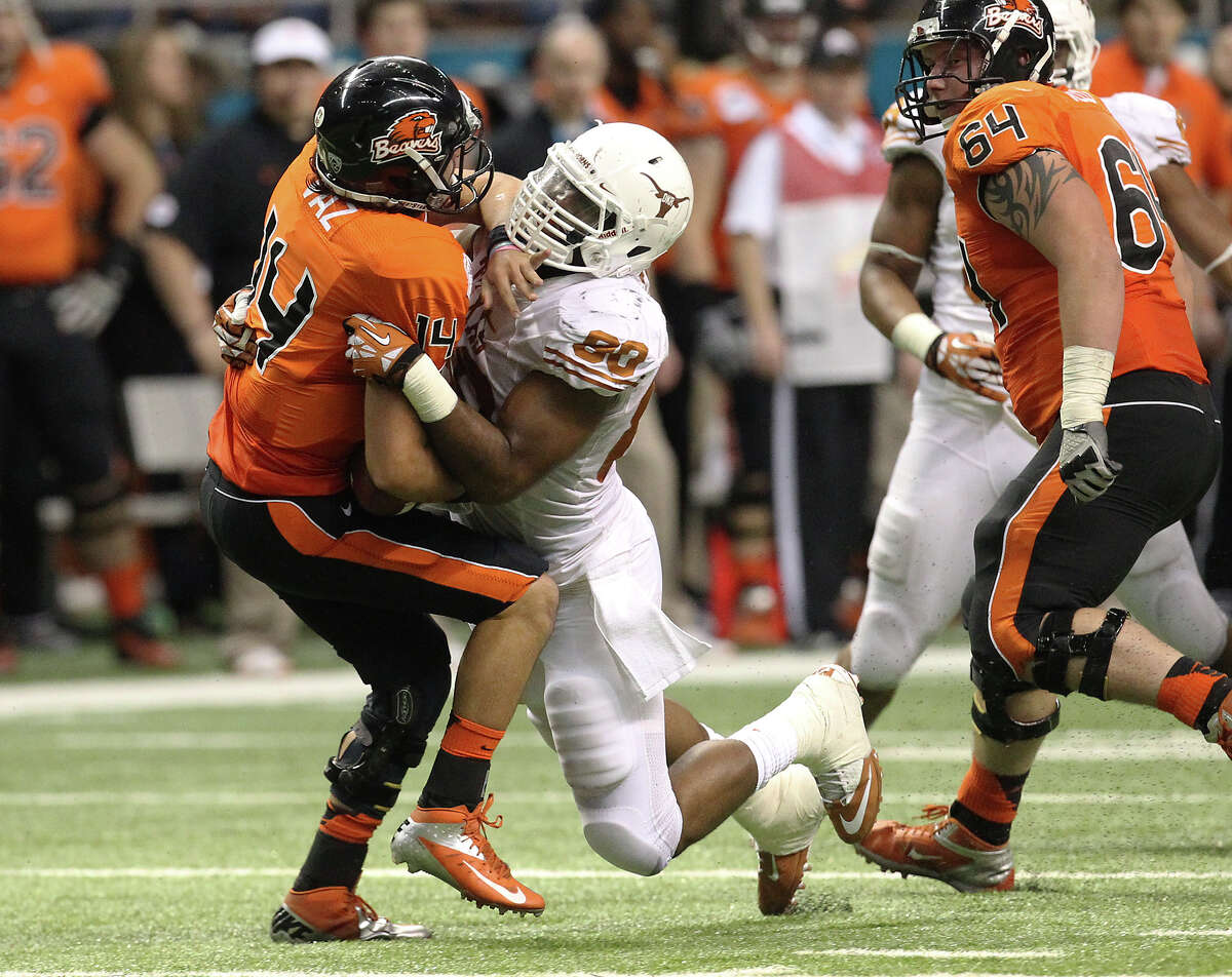 Scattering Beavers Texas defensive end Alex Okafor helped key a fearsome pass rush that sacked Oregon State's Cody Vaz 10 times in the Longhorns' 31-27 comeback victory in the Valero Alamo Bowl.PHOTO: Okafor (80) sacks Vaz (14) in the first half of the Valero Alamo Bowl on Dec. 29, 2012.