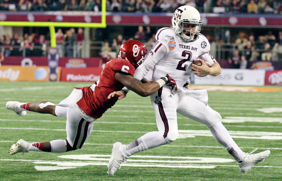 Johnny B. Good So much for any Heisman hangover as Texas A&M quarterback Johnny Manziel set a Cotton Bowl total offense record with 516 yards in an impressive 41-13 rout of Oklahoma. PHOTO: Manziel tries to shake the tackle of Oklahoma's Demontre Hurst during second half of the Cotton Bowl on Jan. 4, 2013 at Cowboys Stadium in Arlington. A penalty was called on the play. Photo: Edward A. Ornelas, San Antonio Express-News / © 2012 San Antonio Express-News