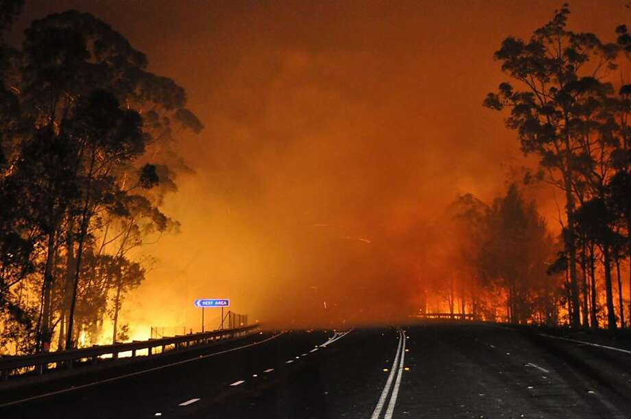 In this photo provided by the New South Wales Rural Fire Service a wildfire near Deans Gap, Australia, crosses the Princes Highway Tuesday, Jan. 8, 2013. Firefighters are battling scores of wildfires in southeastern Australia as authorities evacuate national parks and warned that hot, dry and windy conditions were combining to raise the threat to its highest alert level. Photo: James Morris, Associated Press