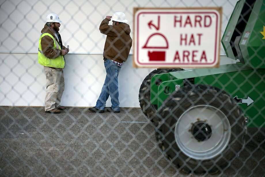 Workers talk at the base of a presidential viewing booth on Pennsylvania Avenue near the White House while structures are built for the upcoming US Presidential inauguration January 8, 2013 in Washington, DC. Preparations continue for the 57th inauguration where President Barack Obama will be sworn in for his second term as US President. Photo: Brendan Smialowski, AFP/Getty Images