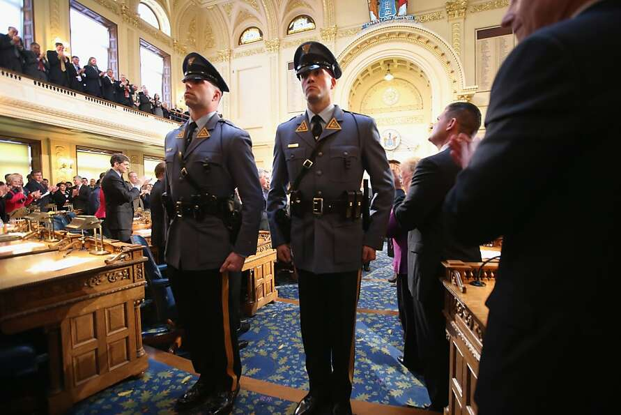 New Jersey state troopers stand escort Governor Chris Christie after his State of the State Address