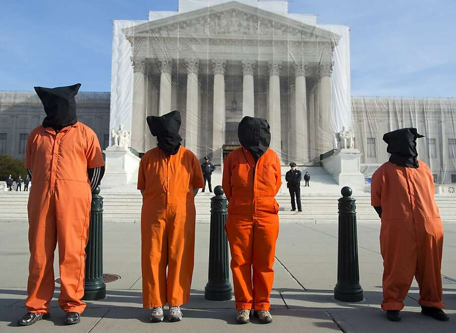 Protestors wear orange prison jump suits and black hoods on their heads during protests against holding detainees at the military prison in Guantanamo Bay during a demonstration in front of the US Supreme Court in Washington, DC, on January 8, 2013. This weeks marks the 11th anniversary of the opening of the prison. Photo: Saul Loeb, AFP/Getty Images