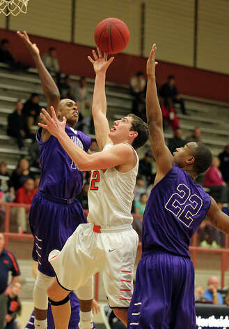 Brandeis' Jared Thompson (32) puts up a shot as Warren's Paris Collins (left) closes in for a block with teammate Avionte Sanders (22) during their game on Tuesday, Jan. 8, 2013. Brandeis defeated Warren, 56-48. Photo: Kin Man Hui, San Antonio Express-News / © 2012 San Antonio Express-News