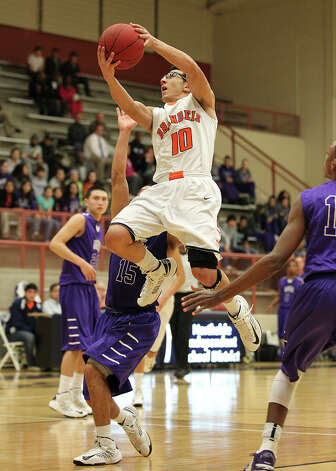 Brandeis' Shawn Guerrero (10) goes strong to the basket against Warren's Adrian Farruggia (15) during their game on Jan. 8. Brandeis defeated Warren, 56-48. Photo: Kin Man Hui, San Antonio Express-News / © 2012 San Antonio Express-News