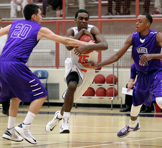 Brandeis' Justin Graham (15) drives to the basket between Warren's Anthony Trevino (20) and Paris Collins (10) during their game on Tuesday, Jan. 8, 2013. Brandeis defeated Warren, 56-48. Photo: Kin Man Hui, San Antonio Express-News / © 2012 San Antonio Express-News