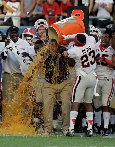 Georgia head coach Mark Richt, center, is doused by his players including free safety Marc Deas (23)