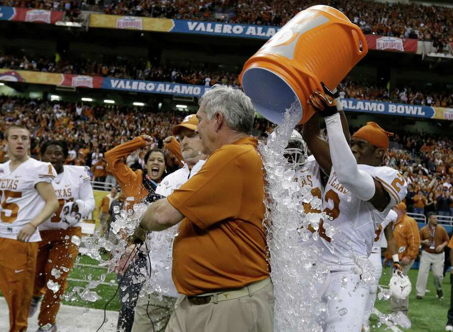 Texas head coach Mack Brown, center, is dunked by players after they defeated Oregon State in the Alamo Bowl NCAA football game, Saturday, Dec. 29, 2012, in San Antonio.  Texas won 31-27. (AP Photo/Eric Gay) Photo: Eric Gay, Associated Press / AP