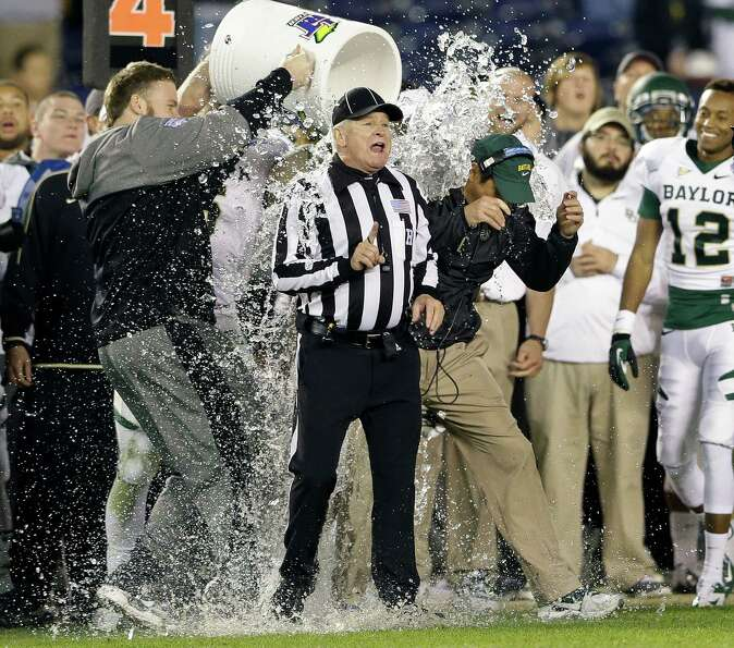 Baylor coach Art Briles is doused next to an official after Baylor defeated UCLA 49-26 in the Holida