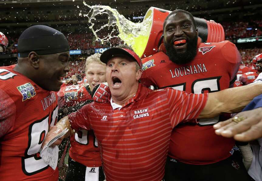 Louisiana-Lafayette head coach Mark Hudspeth is dunked at the end of a win over East Carolina in the