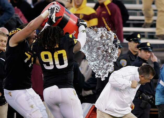 Head coach Todd Graham of the Arizona State Sun Devils is dumped with water by Will Sutton #90 of the Arizona State Sun Devils after they beat the Navy Midshipmen in the Kraft Fight Hunger Bowl at AT&T Park on December 29, 2012 in San Francisco, California. Photo: Ezra Shaw, Getty Images / 2012 Getty Images