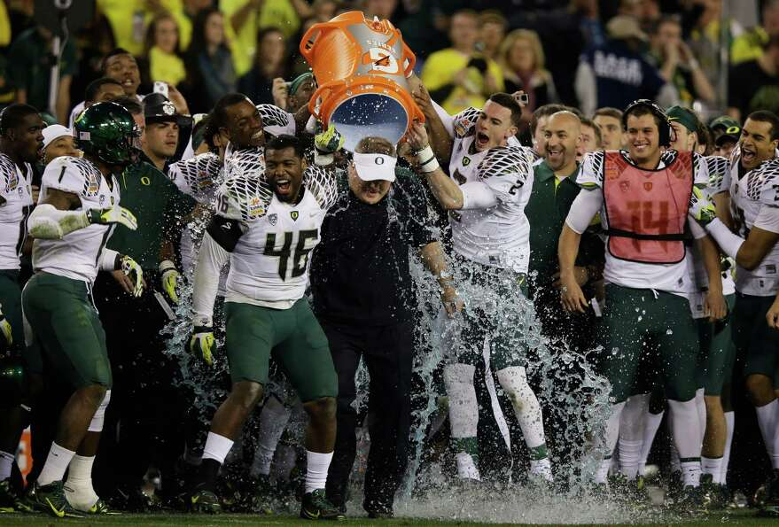 Michael Clay #46 and Bryan Bennett #2 dump the Gatorade cooler on head coach Chip Kelly of the Orego