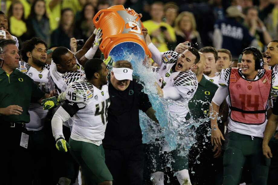 Michael Clay #46 and Bryan Bennett #2 dump the Gatorade cooler on head coach Chip Kelly of the Oregon Ducks after their 35 to 17 victory over the Kansas State Wildcats in the Tostitos Fiesta Bowl at University of Phoenix Stadium on January 3, 2013 in Glendale, Arizona. Photo: Ezra Shaw, Getty Images / 2013 Getty Images