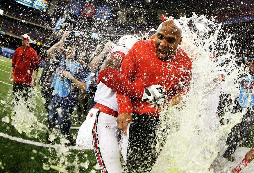 The Gatorade bucket is dumped on head coach Charlie Strong of the Louisville Cardinals after their 3