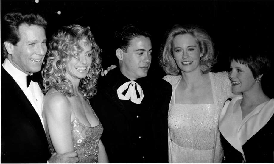 "Then: Robert Downey Jr. (center) is surrounded by Ryan O'Neal (from left) Farrah Fawcett, Cybill Shepherd, and Mary Stuart Masterson on March 5, 1989, at the New York premiere of their new film, ""Chances Are."" Photo: Ray Stubblebine, AP / AP1989"