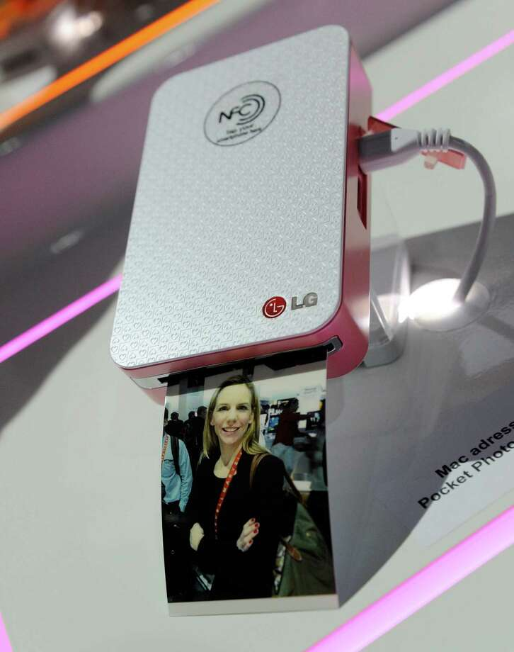LAS VEGAS, NV - JANUARY 08:  A photograph emerges from a LG Pocket Photo printer that uses NFC technology  at the 2013 International CES at the Las Vegas Convention Center on January 8, 2013 in Las Vegas, Nevada. CES, the world's largest annual consumer technology trade show, runs through January 11 and is expected to feature 3,100 exhibitors showing off their latest products and services to about 150,000 attendees. Photo: David Becker, Getty Images / 2013 Getty Images