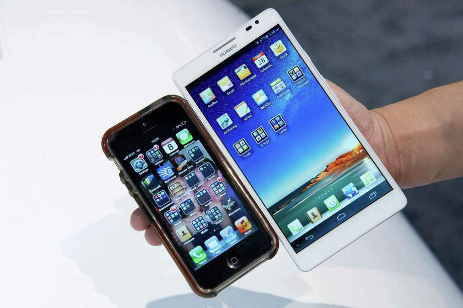 A Huawei Technologies Co. Ascend Mate smartphone, right, and an Apple iPhone 5 are arranged for a photograph on Tuesday. Photo: David Paul Morris, Bloomberg / © 2013 Bloomberg Finance LP