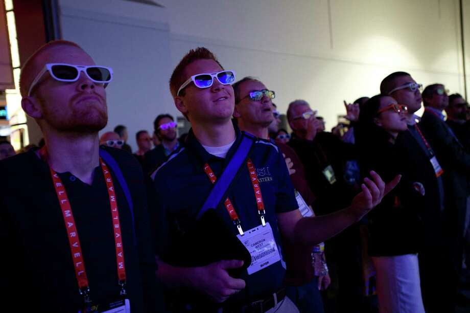 Attendees wearing 3D glasses watch a video presentation at the LG Electronics Inc. booth Tuesday. Photo: David Paul Morris, Bloomberg / © 2013 Bloomberg Finance LP