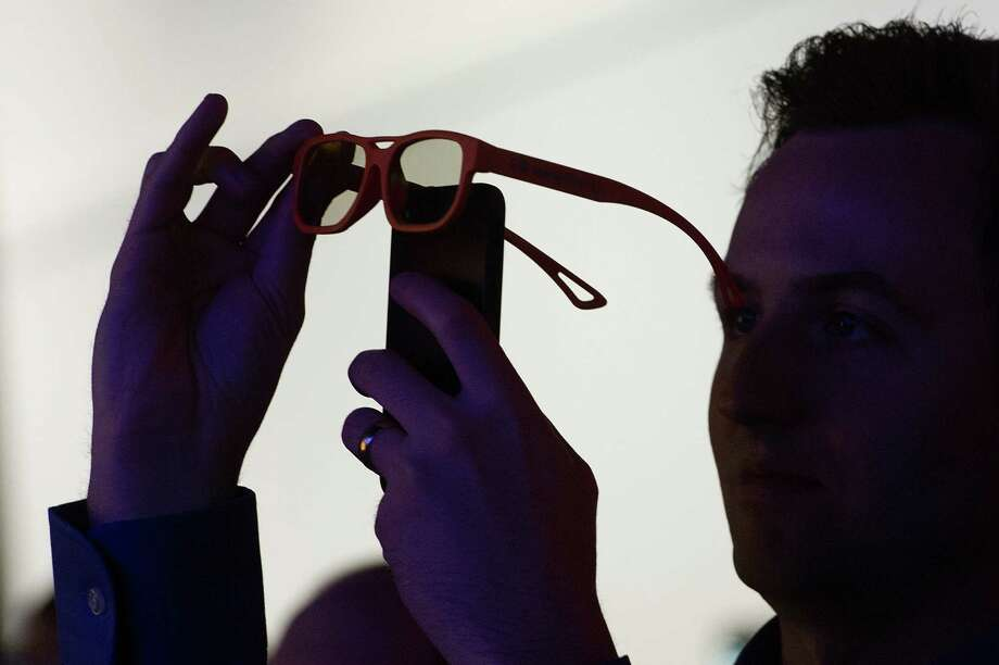 An attendee uses a smartphone to shoot a video through 3D glasses during a video presentation at the LG Electronics Inc. booth. Photo: David Paul Morris, Bloomberg / © 2013 Bloomberg Finance LP