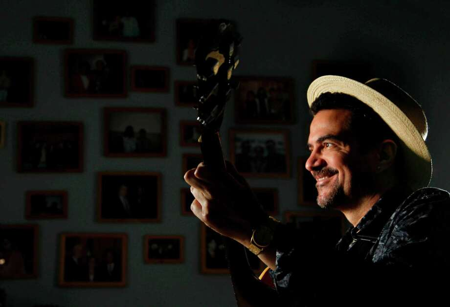 Hispanic latin-rock singer Walter Suhr, leader of the band Mango Punch, plays the guitar in his music studio where he has photographs of all the artist he was meet over his career on Tuesday, Sept. 13, 2011, in Houston. Suhr is celebrating his 20 years aniversary as a profesional musician with an special concert. ( Mayra Beltran / Houston Chronicle ) Photo: Mayra Beltran, Staff / © 2011 Houston Chronicle