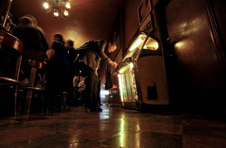 Anna Delorefice, picks out a song on the jukebox at Tosca Cafe. (The Chronicle)