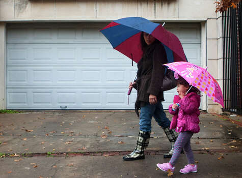 "Danielle Harris, 3, looks up at her umbrella as she walks along Kingston Street, with her mom, Betty Harris, Wednesday, Jan. 9, 2013, in Houston. ""I can't believe it's been raining this much,"" Betty said. Photo: Cody Duty, Houston Chronicle / © 2012 Houston Chronicle"