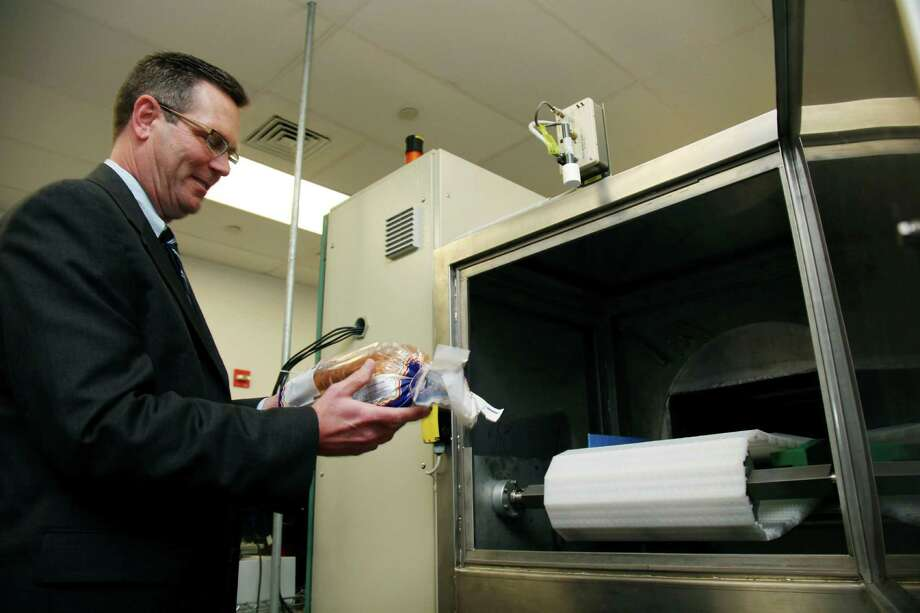 In this Dec. 6, 2012, photo, Don Stull, chief executive officer of Microzap, Inc., places a loaf of bread inside a patented microwave that kills mold spores in Lubbock, Texas. The company claims the technology allows bread to stay mold-free for 60 days. (AP Photo/John Mone) Photo: John Mone