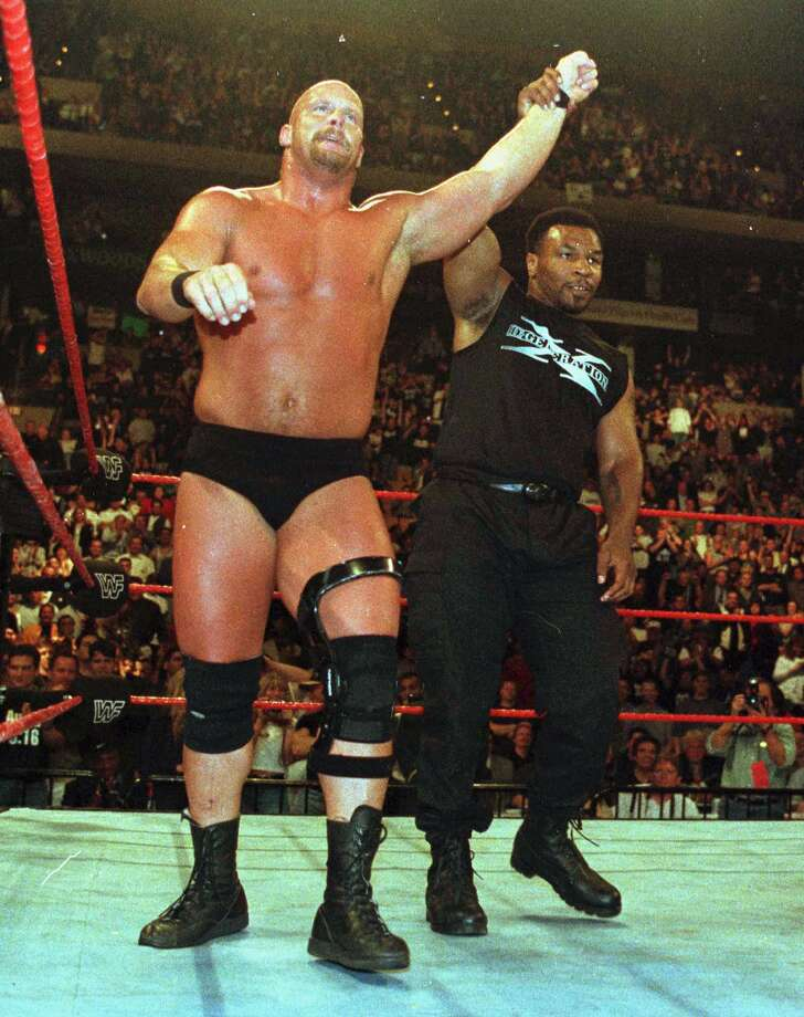 Boxer Mike Tyson, right, holds the arm of winner Stone Cold Steve Austin following Austin's defeat of Shawn Michaels. Photo: WINSLOW TOWNSON, AP / AP