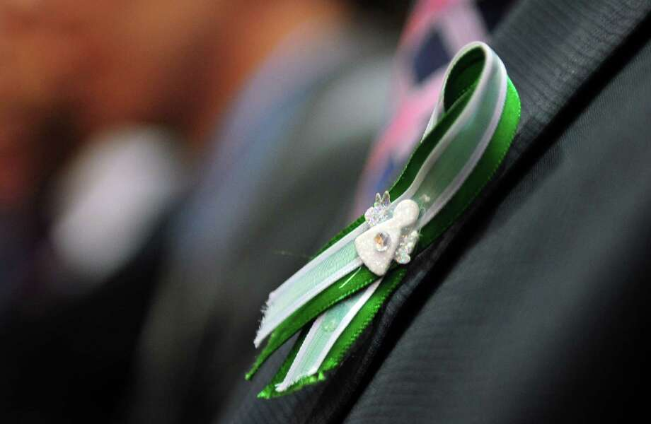 Members of the General Assembly marked the Newtown tragedy by the wearing of green and white ribbons Wednesday, Jan. 9, 2013 during opening day of the State Legislature at the Capitol Building in Hartford, Conn. Photo: Autumn Driscoll / Connecticut Post