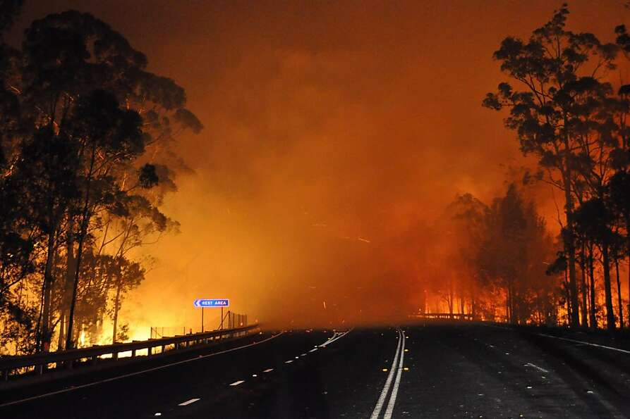 Into the burn zone: The Princes Highway disappears into blazing trees and billowing smoke at