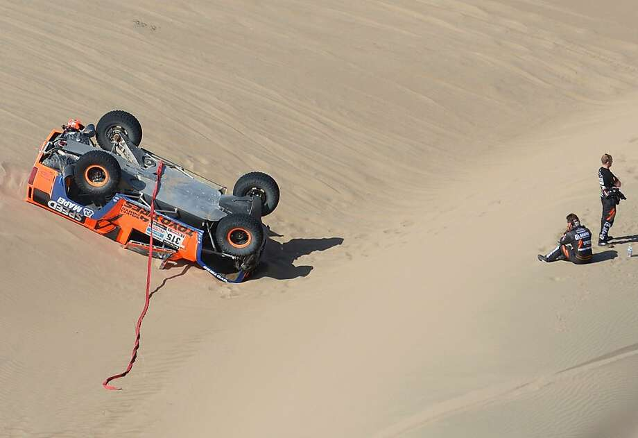 Hummer bummer: Even from a distance, American Robby Gordon (far right) and his co-driver look dejected after flipping their Hummer during Stage 4 of the Dakar 2013 between Nazca and Arequipa, Peru. The mishap left Gordon almost six hours behind the leader. Photo: Franck Fife, AFP/Getty Images