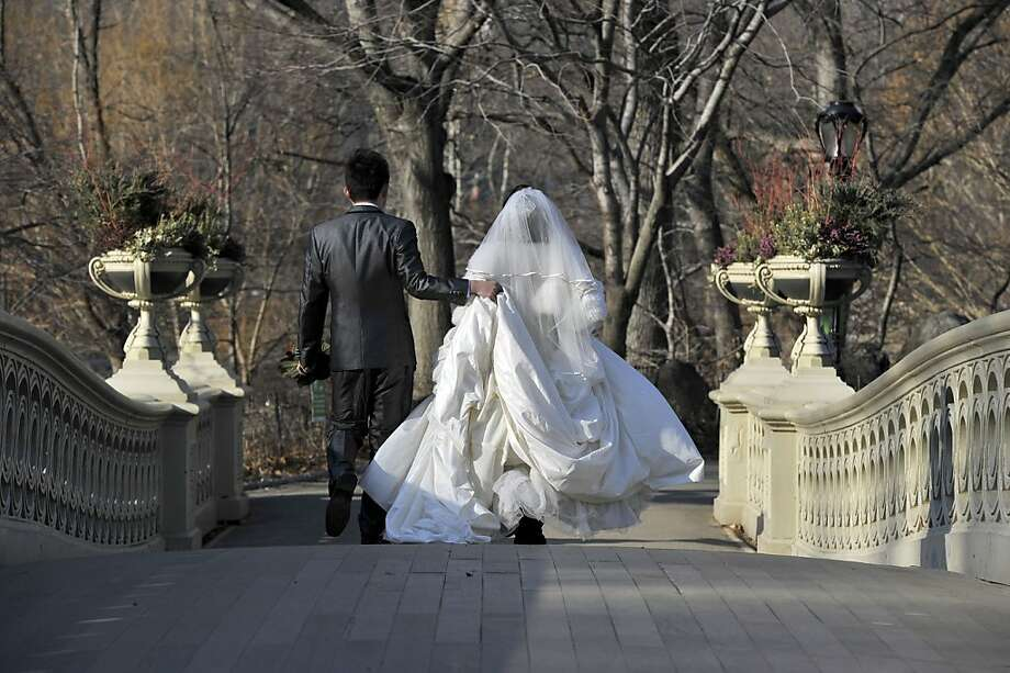 Big balmy Apple:Newlyweds headed to their wedding shoot cross Central Park's Bow Bridge during unusually warm weather for January. Photo: Timothy A. Clary, AFP/Getty Images
