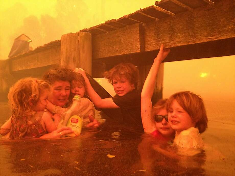 Refuge under the pier:Tammy Holmes and her grandchildren take refuge under a jetty as a wildfire rages around them in the Tasmanian town of Dunalley, Australia. All survived the blaze, which destroyed 90 homes. Photo: Tim Holmes, Associated Press