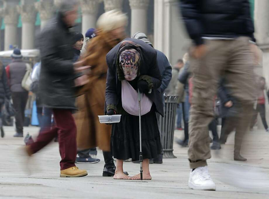 A barefoot woman begs for money in downtown Milan. Photo: Antonio Calanni, Associated Press